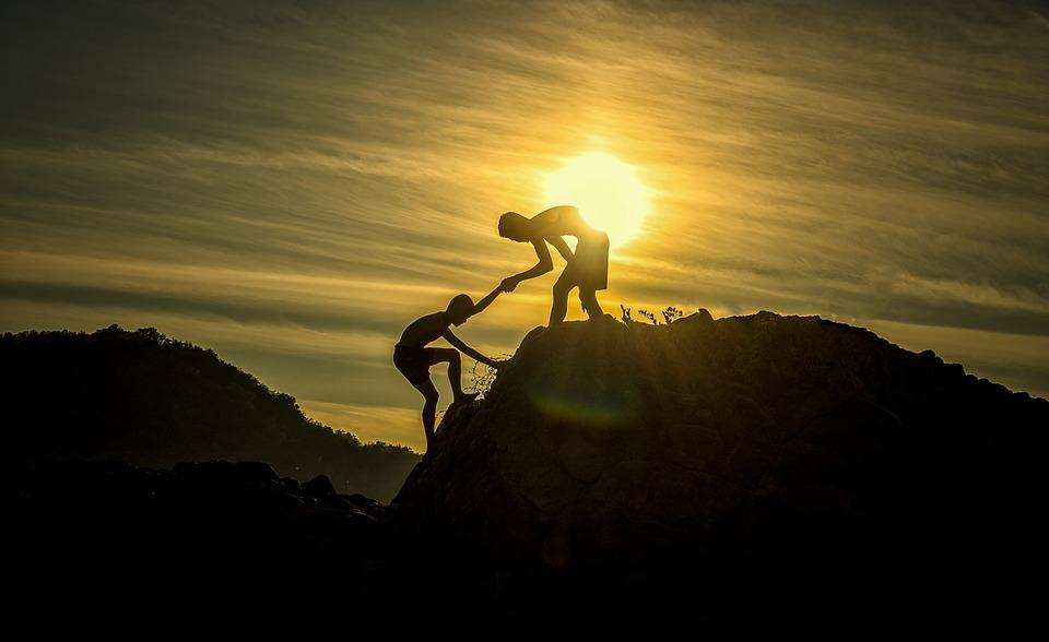 A picture of a person helping others climb a mountain