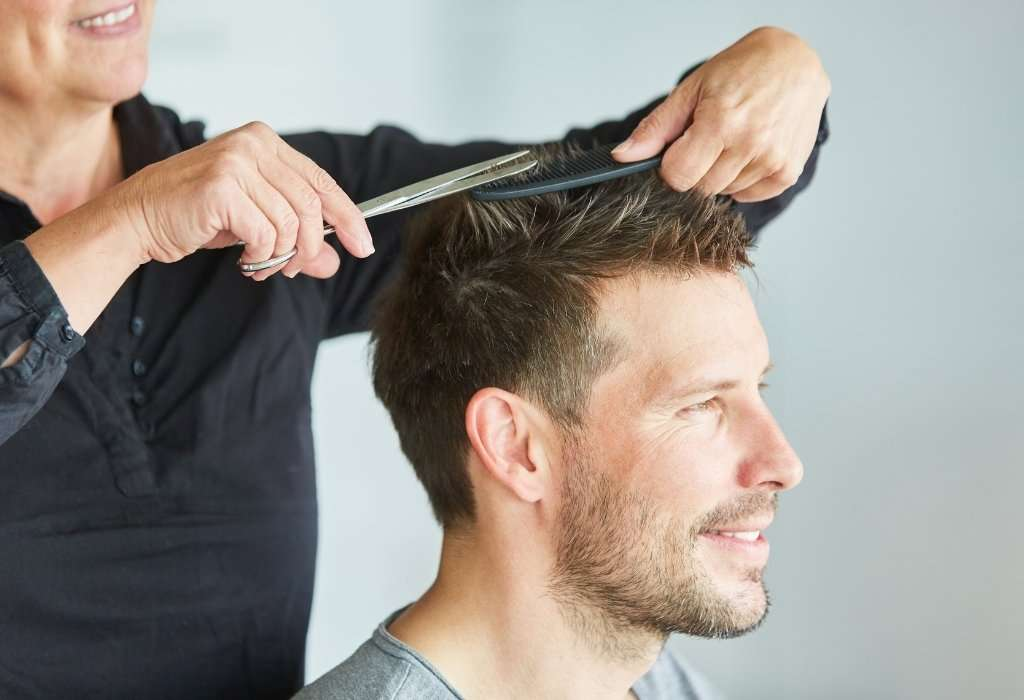 woman cuts man's hair with scissors