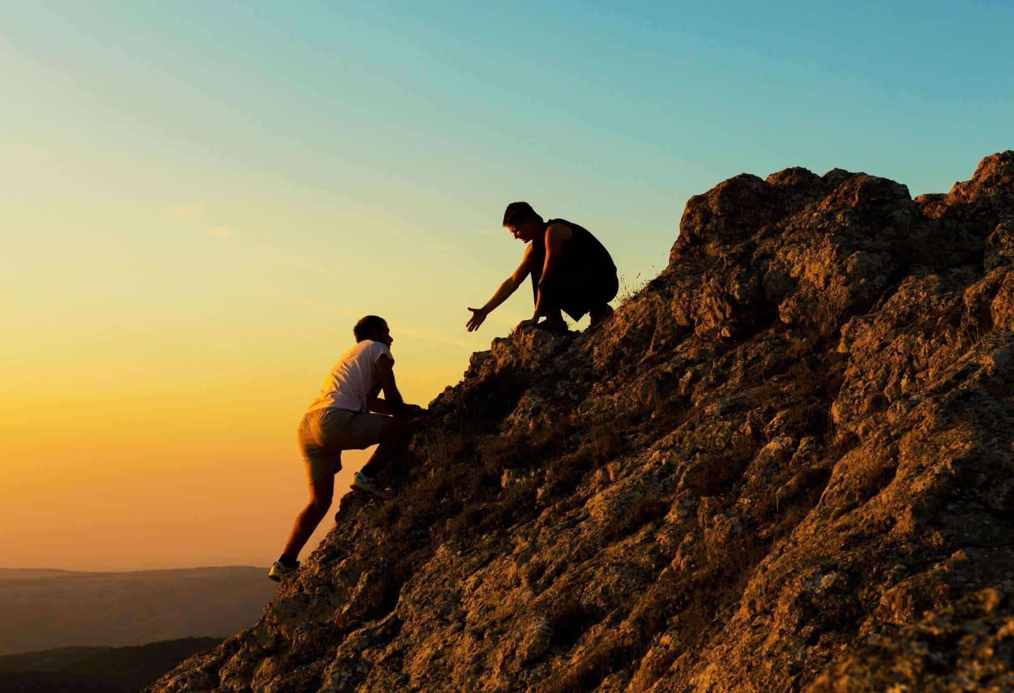 men helping each other climb the rock